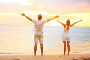 Happy cheering couple enjoying sunset at beach with arms raised